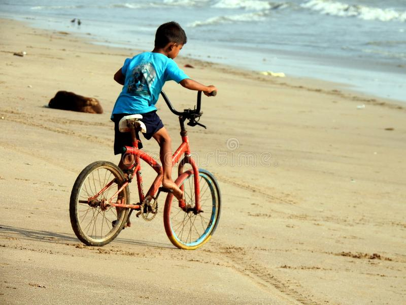 Little boy learning how to ride a bike on cleaned up Versova beach, Mumbai. royalty free stock image