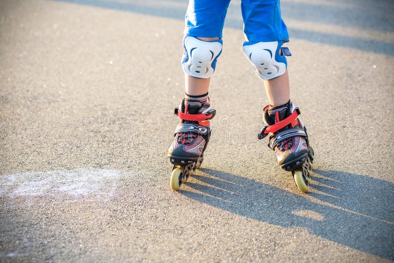 Little boy learning to roller skate in summer park. Children wearing protection pads for safe roller skating ride. Active outdoor. Sport for kids. Close up view royalty free stock photography