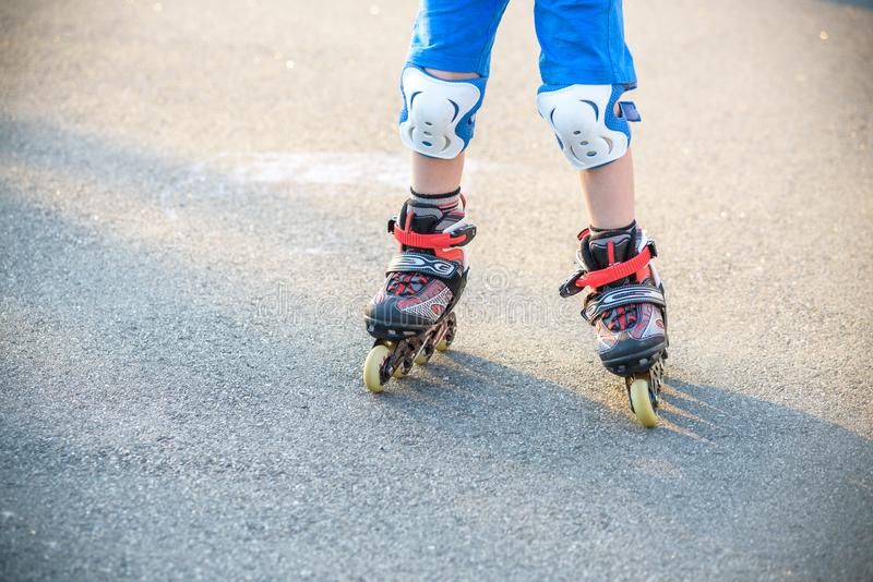 Little boy learning to roller skate in summer park. Children wearing protection pads for safe roller skating ride. Active outdoor. Sport for kids. Close up view royalty free stock photo