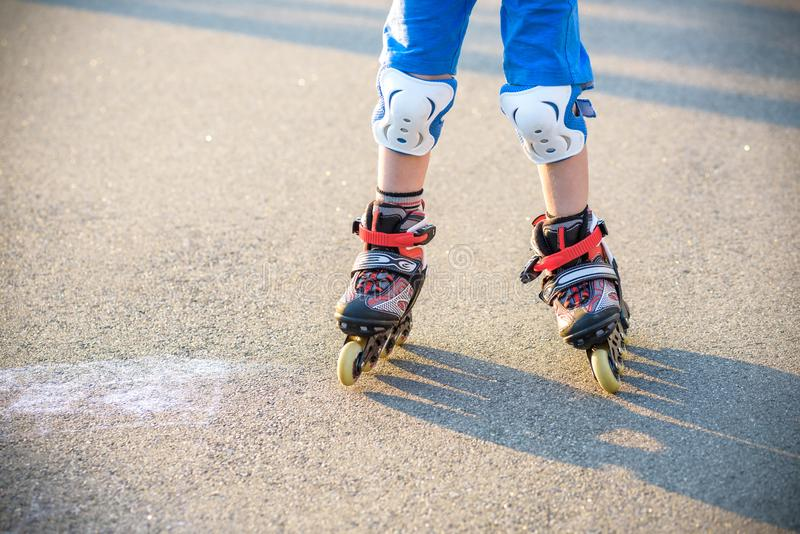 Little boy learning to roller skate in summer park. Children wearing protection pads for safe roller skating ride. Active outdoor. Sport for kids. Close up view royalty free stock images