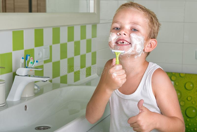 Little boy learning to shave.Wants to be like dad. Wants to be like dad.Little boy learning to shave stock images