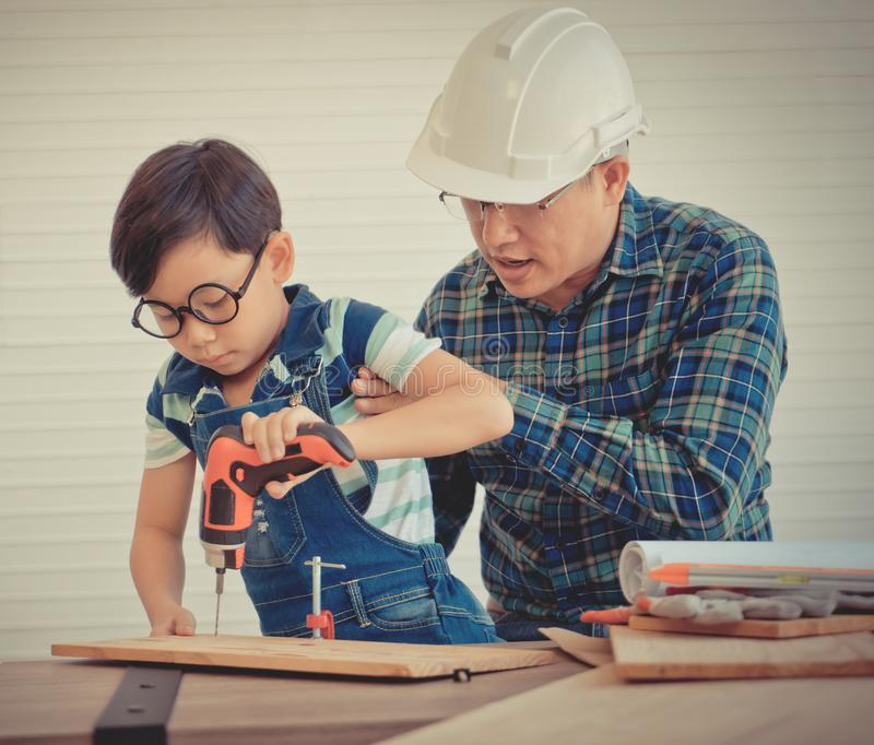 Little Boy is learning to work on wood and be a builder from his craftman father in vintage tone for Parenting and fatherhood. Concept royalty free stock photography