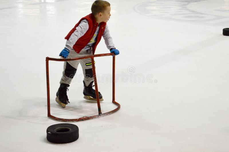 Little boy learns to skate with the help of special supporting gates on the ice hockey arena, April 14, 2018, Belarus stock photo
