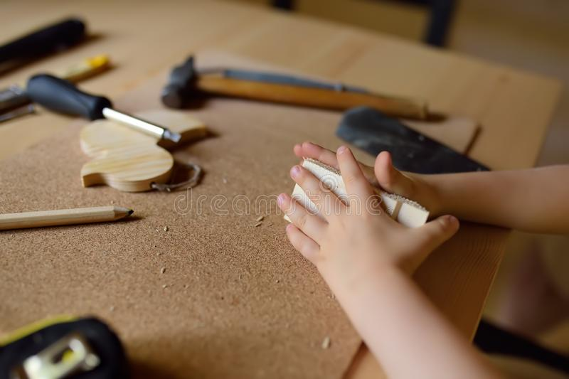 Little boy learns work with tools. Kid make a wooden toy. Close up. Traditional education of boy. Family`s values. Dad`s. Upbringing. Safety stock photos