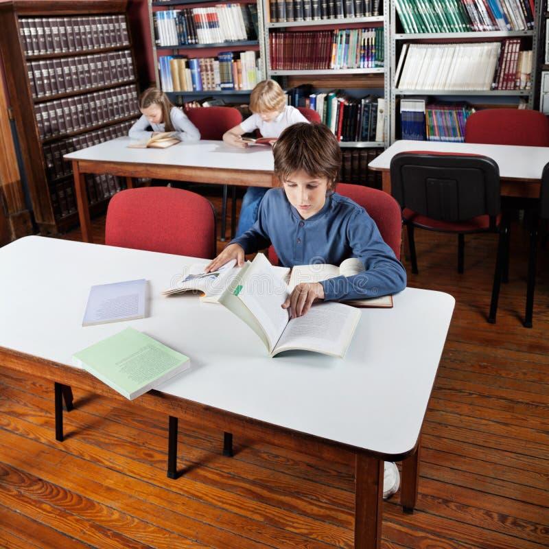 Little Boy-Lesebücher in der Bibliothek stockfoto