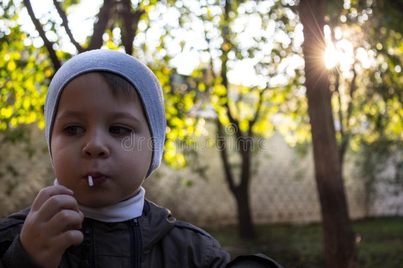 A little boy licking a lollipop in the street stock photo