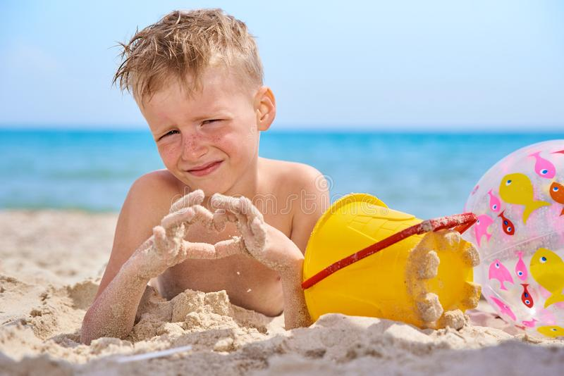 LITTLE BOY LIES ON SEA SANDY BEACH royalty free stock images