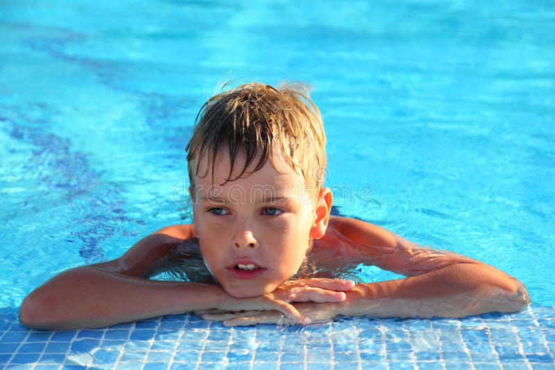 Little boy lies in swimming-pool royalty free stock photo
