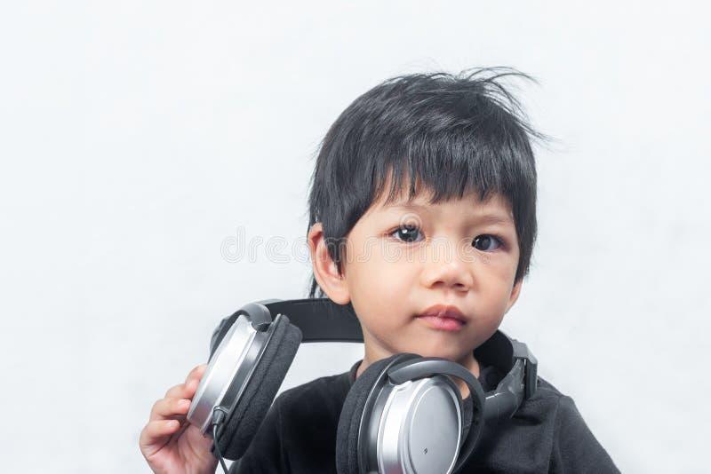Little Boy lindo con el auricular en el fondo blanco imagen de archivo