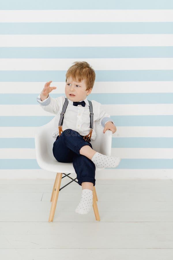 Little Boy lindo que se sienta en niño descontentado silla imágenes de archivo libres de regalías