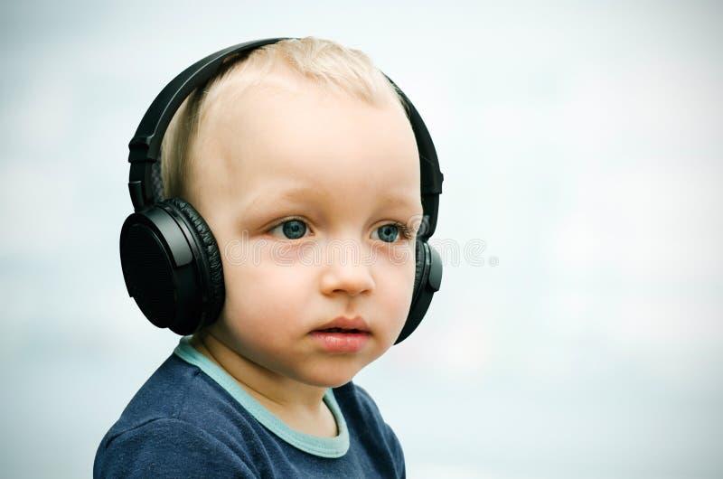Little boy listens to music. Llittle boy listens to music through wireless headphones stock images
