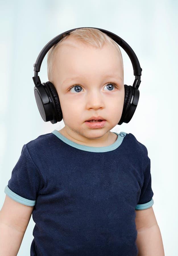 Little boy listens to music. Through wireless headphones stock photo