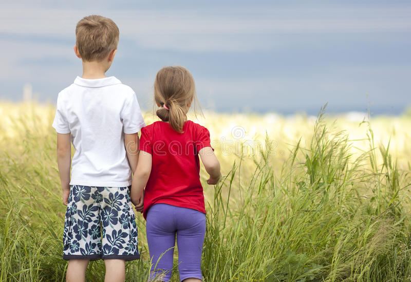 Little boy and little girl standing holding hands looking on horizont. Little boy and little girl standing holding hands looking horizont stock image