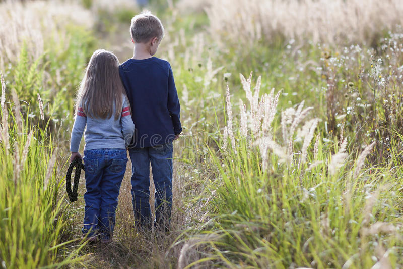 Little boy and little girl standing holding hands looking on horizont. Rear view. stock image