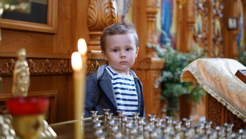 Little boy look at the candle in Orthodox Church, first visit to aChurch royalty free stock images