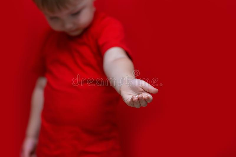 Little boy look down and pulls his hand to camera, kid wanted help for him stock images