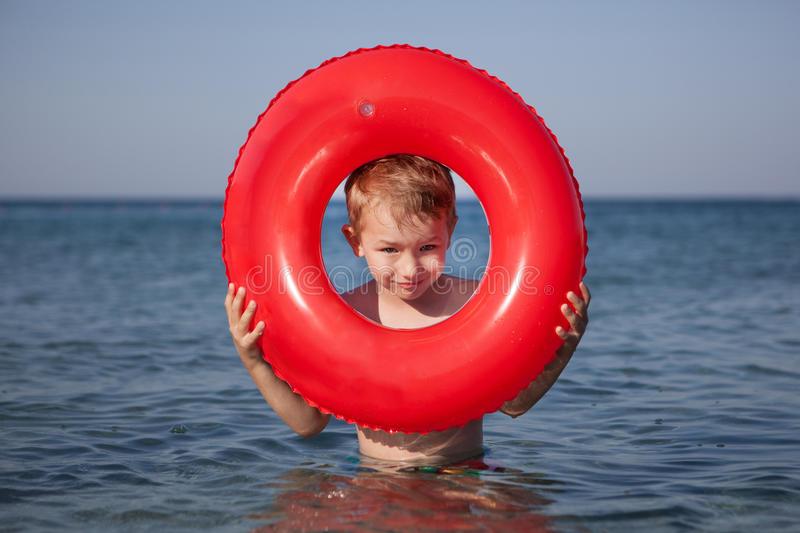 Little boy look out of inflatable ring in the sea stock photos