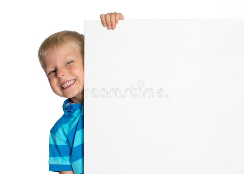 A little boy is looking from behind an empty banner. A little boy looks through an empty banner on which you can write any text. The concept of a happy royalty free stock images