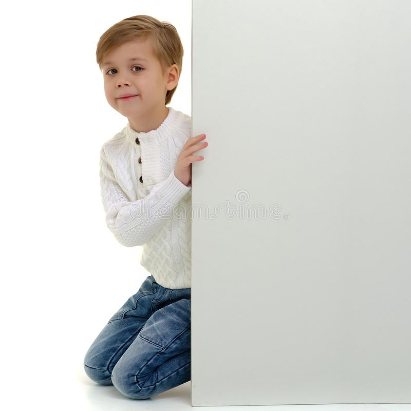 A little boy is looking from behind an empty banner. A little boy looks through an empty banner on which you can write any text. The concept of a happy royalty free stock photography