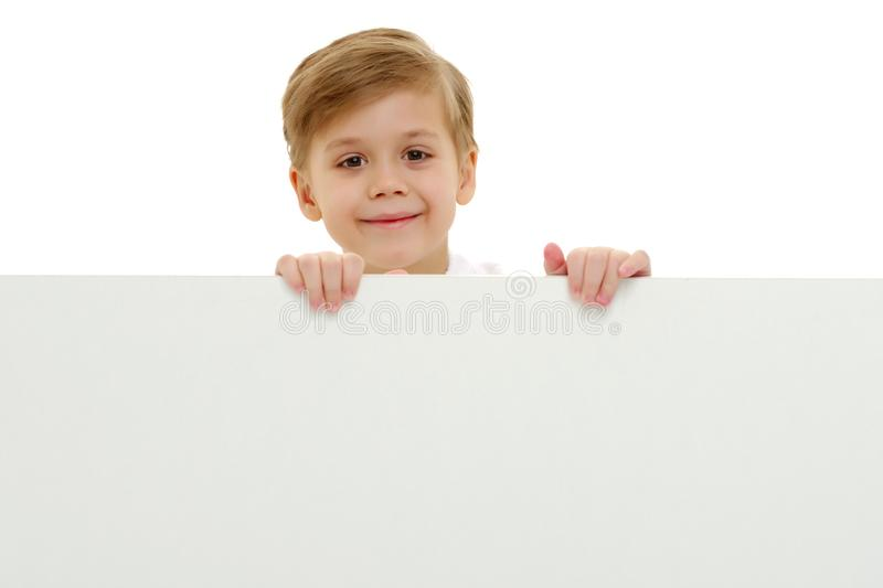 A little boy is looking from behind an empty banner. A little boy looks through an empty banner on which you can write any text. The concept of a happy royalty free stock image