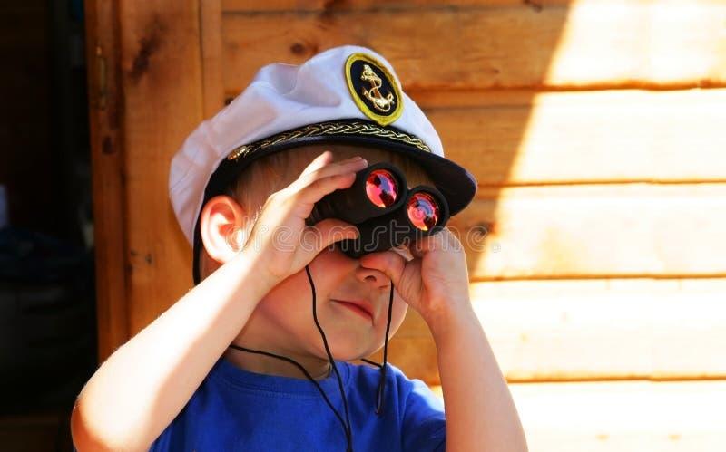 Little boy looking through the binocular stock images