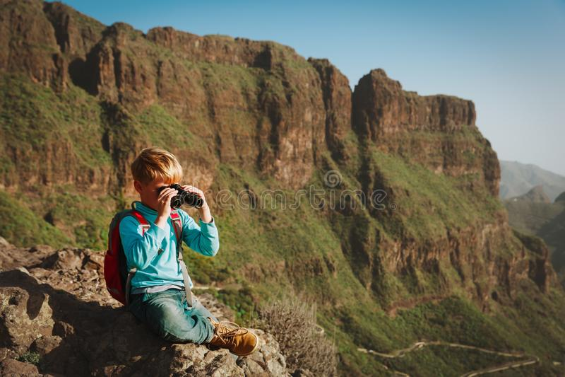 Little boy looking through binoculars travel in mountains stock photo