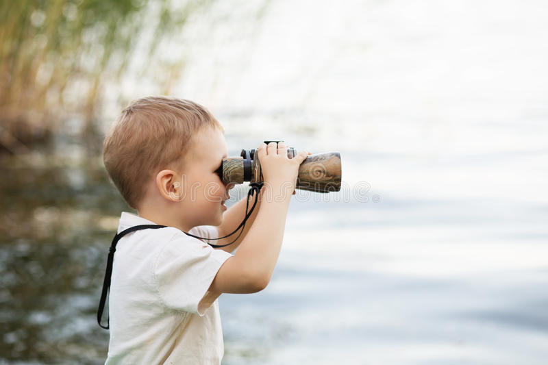 Little boy looking through binoculars on river bank. Portrait of little boy looking through binoculars on river bank. Cute kid with binoculars sitting on the royalty free stock photo