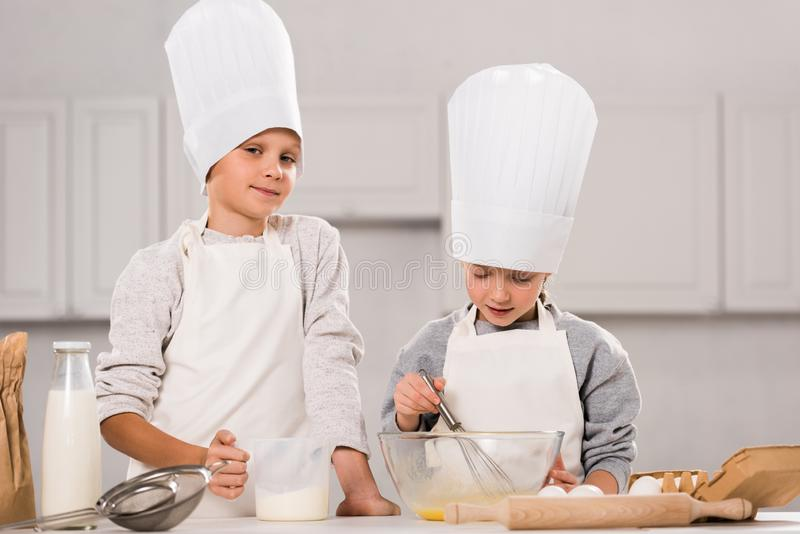 Little boy looking at camera and his sister whisking eggs in bowl at table. In kitchen royalty free stock photo