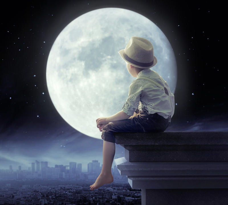 Little boy looking a the city in the night stock image