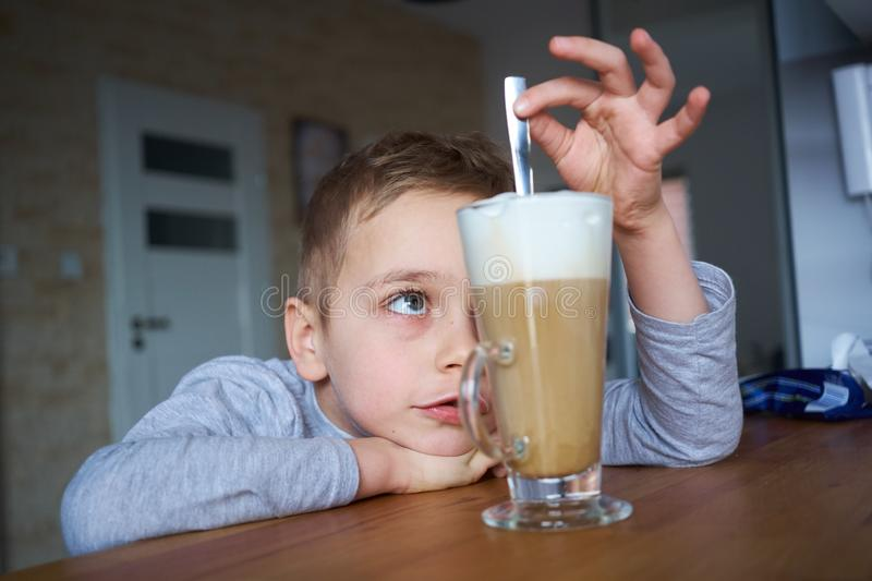 The little boy is looking at coffee royalty free stock photography