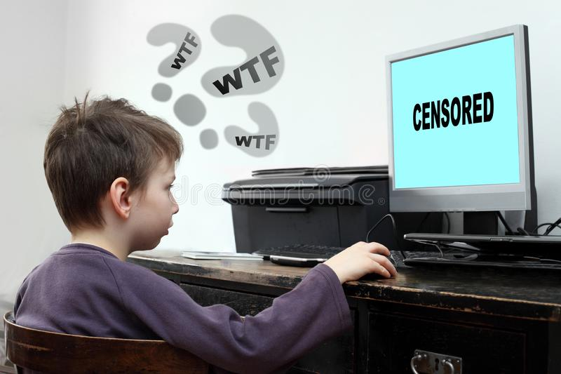 Little boy looking at computer with censored content. stock image