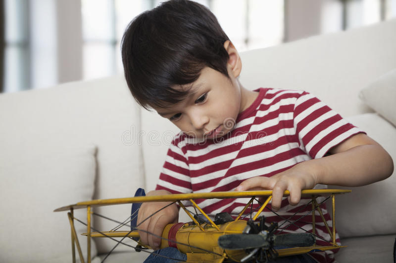Little boy looking down and holding a model airplane, on the couch in the living room royalty free stock photo