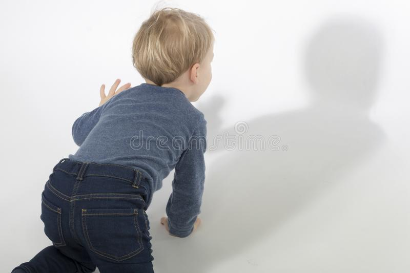 Little boy looking at his shadow in white background with hard light. Studio shot. Copy space royalty free stock photos