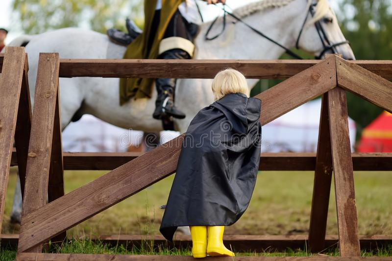Little boy looking on medieval knight riding horse stock photos