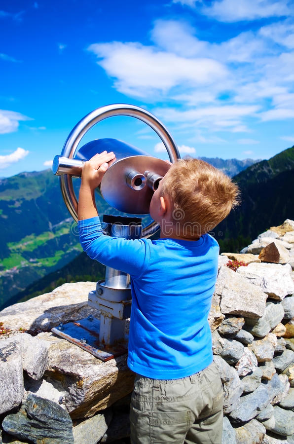 Little boy looking at the mountains through telescope stock photography