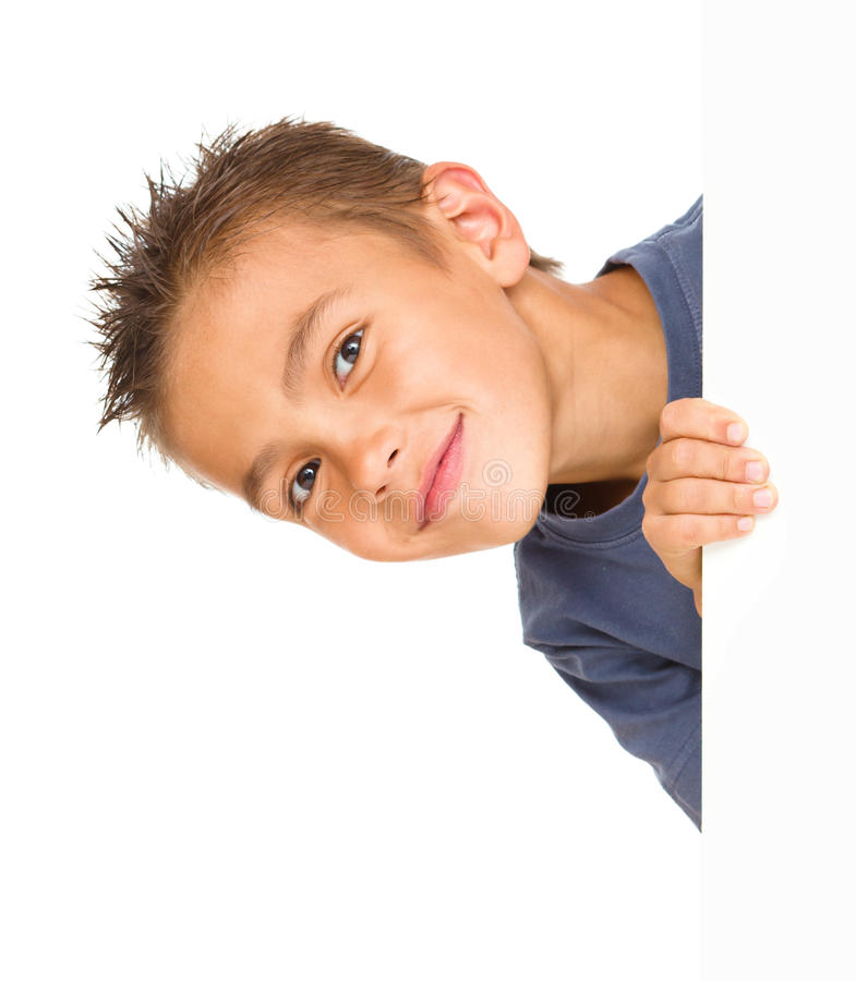 Little boy is looking out from the blank banner. Isolated over white royalty free stock photo
