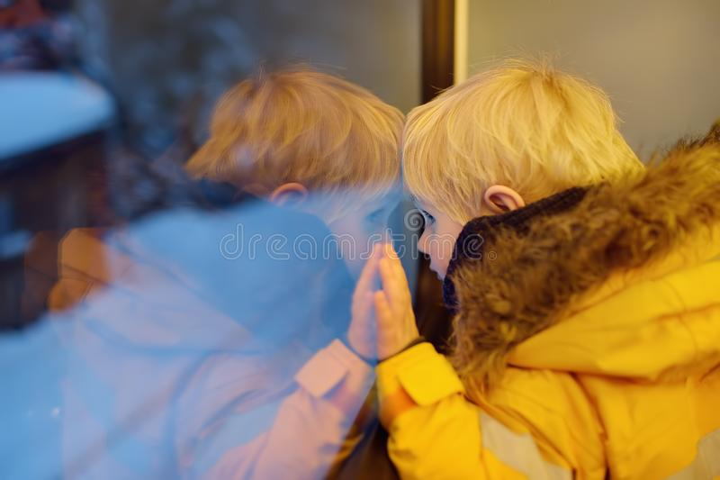 Little boy looking out of the window of train during travel on cogwheel railway/rack railway in Alps mountains royalty free stock image