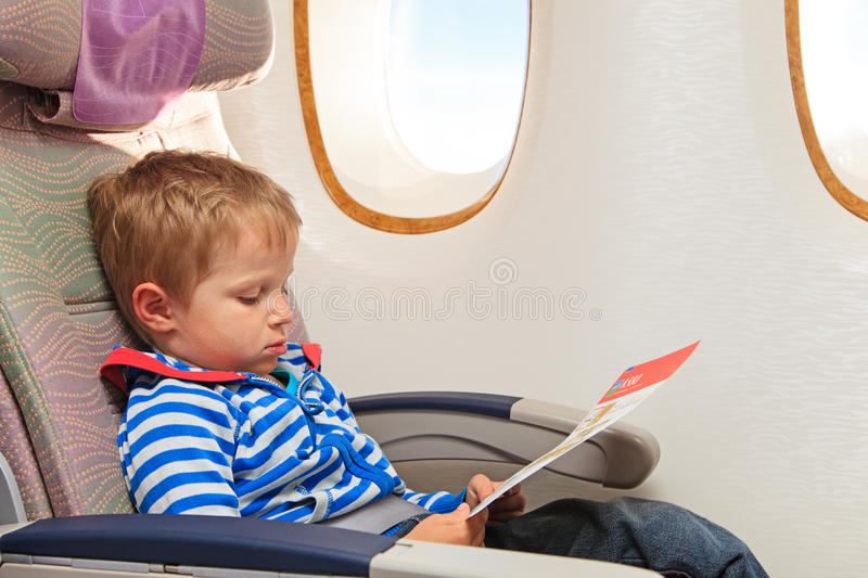 Little boy looking at safety instruction in flight. Travel concept royalty free stock photos