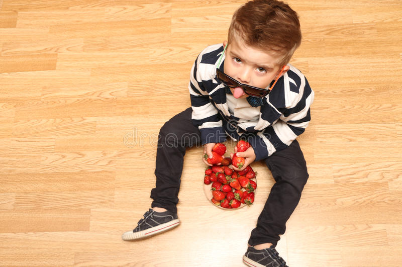 Little boy looking up. Boy picked up a strawberry and looks up from under the tongue showing points stock image