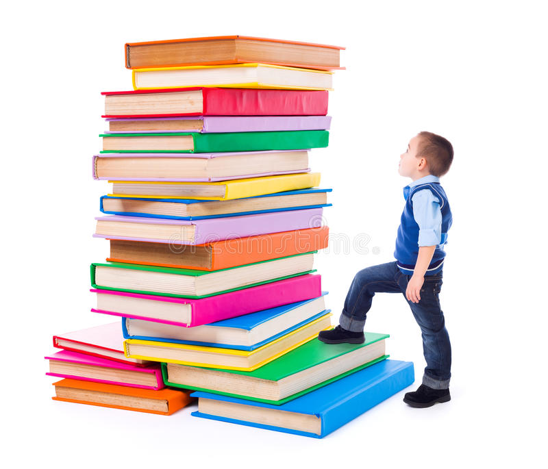 Little boy looking up to stacked big books stock photos