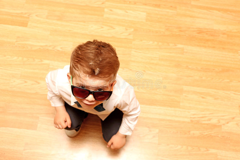 Little boy looking upwards to you. Little boy dressed in classical robes in red glasses looks upwards stock photo
