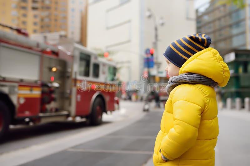 Little boy looks on fire engine. New York, USA. Little boy`s dream concept stock image