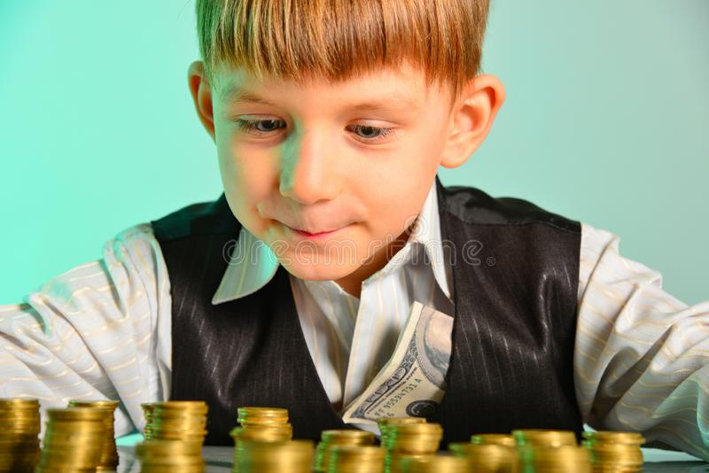 The little boy looks at his cash savings with pleasure. The greedy and vicious concept of the economy of the children`s business.  royalty free stock photo