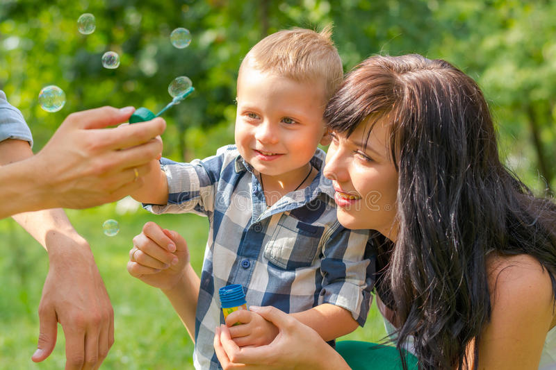 A little boy looks on a soap bubbles. Dad holds his son`s hand a. Nd teaches him to blow soap bubbles. Mom sits by and looks. Family resting in the park royalty free stock photography