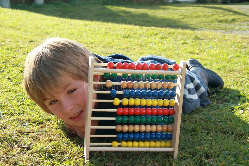 Download Little Boy Lying Behind An Abacus Stock Image - Image of green, grass: 21817749