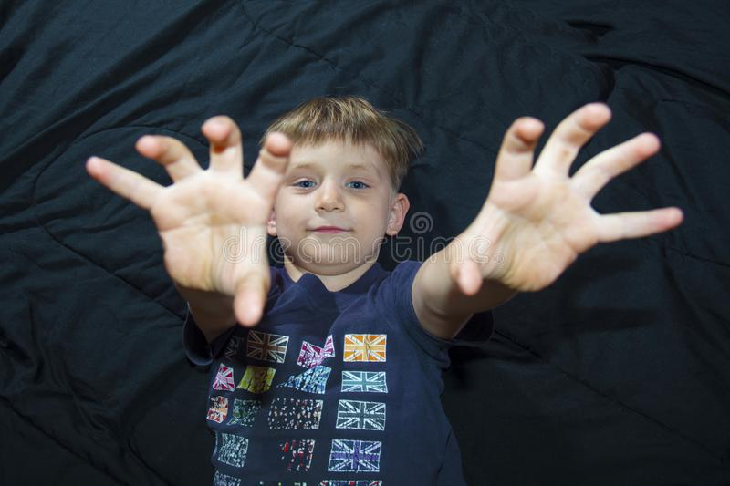 A little boy is lying on the couch and looks at the camera and raises his hands up. royalty free stock photo