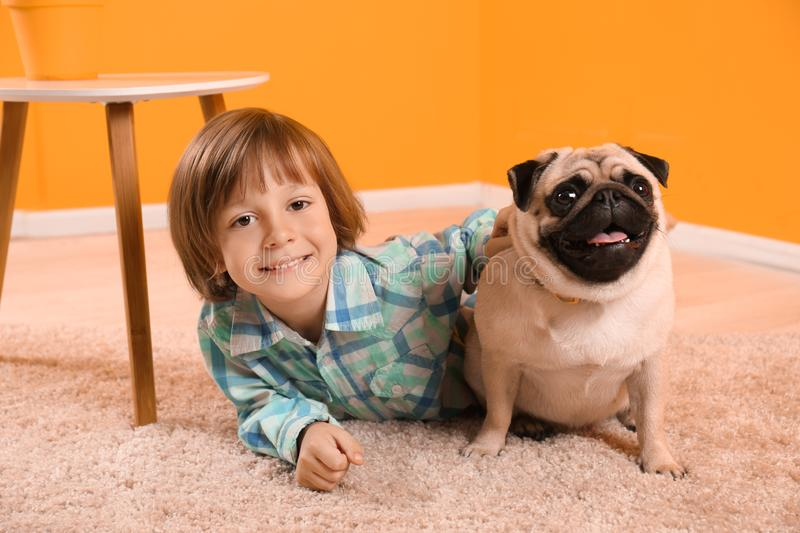 Little boy lying with cute pug dog on floor at home stock image