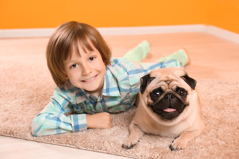 Little boy lying with cute pug dog on floor at home royalty free stock images