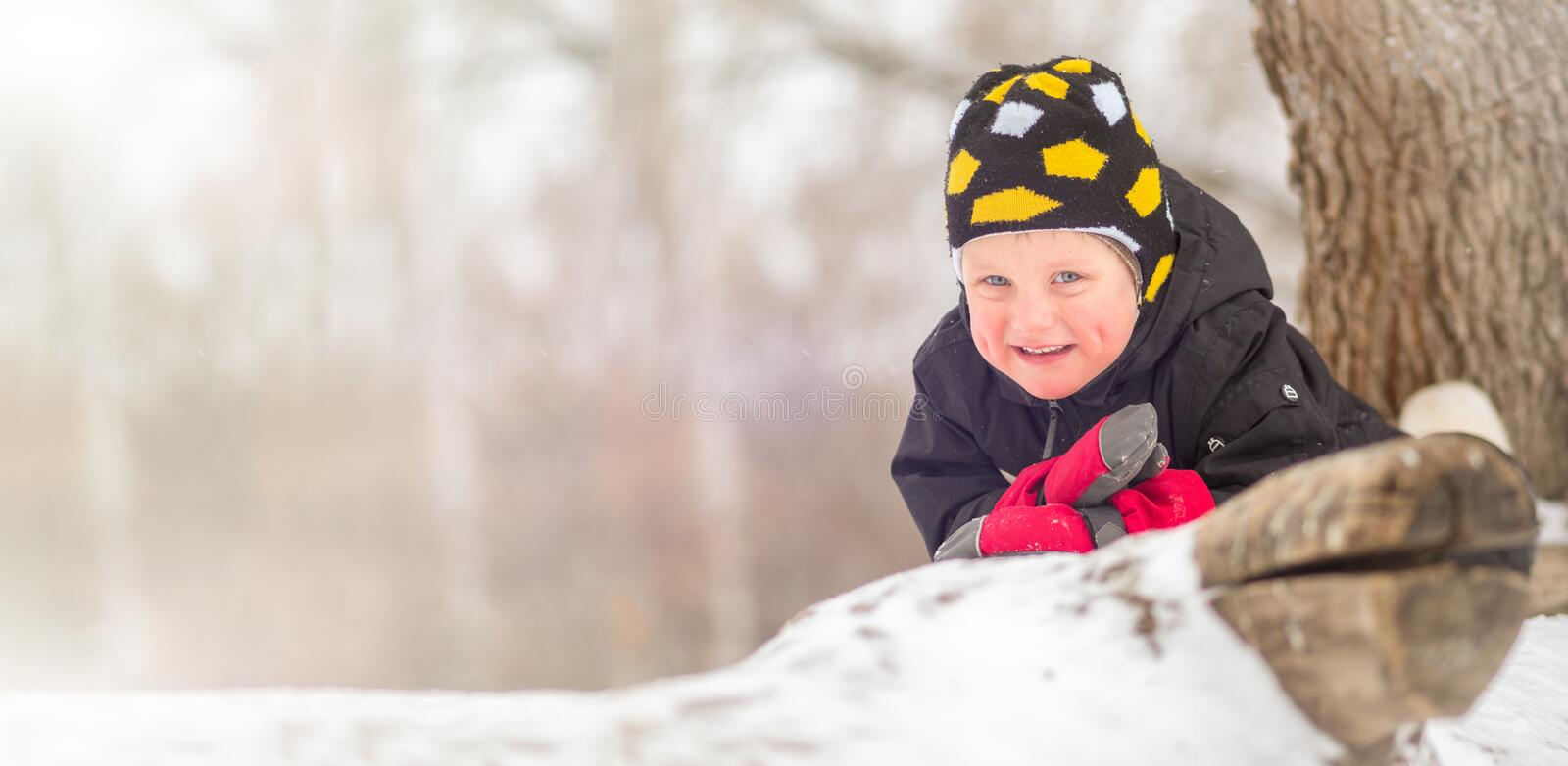 Little boy lying on the snow in winter royalty free stock photos