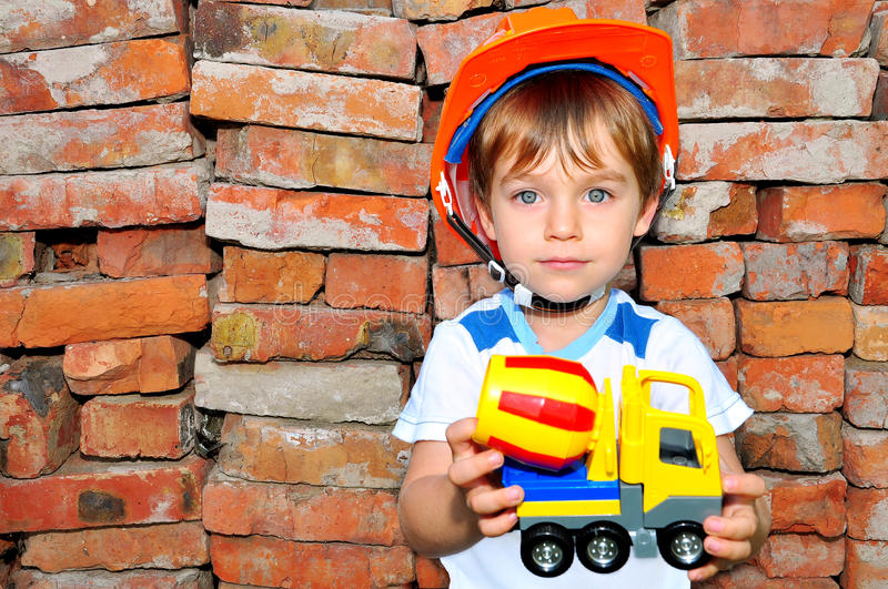 Little boy with machine. Little boy with a machine in his hands against the bricks royalty free stock images